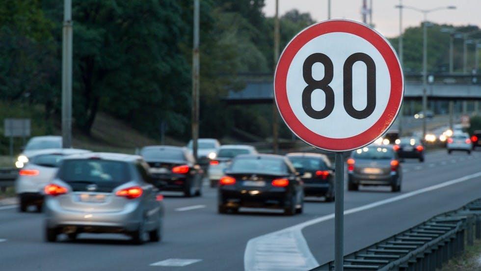 Vehicules ralentissant a hauteur d'un panneau indiquant 80 km/h