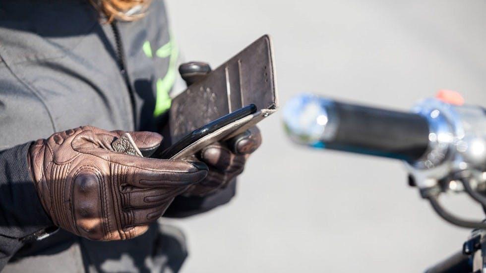 Conductrice de moto utilisant son smartphone comme assistant de navigation