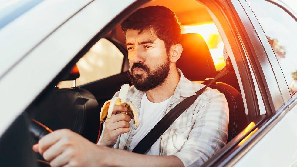 Conducteur mangeant une banane en conduisant