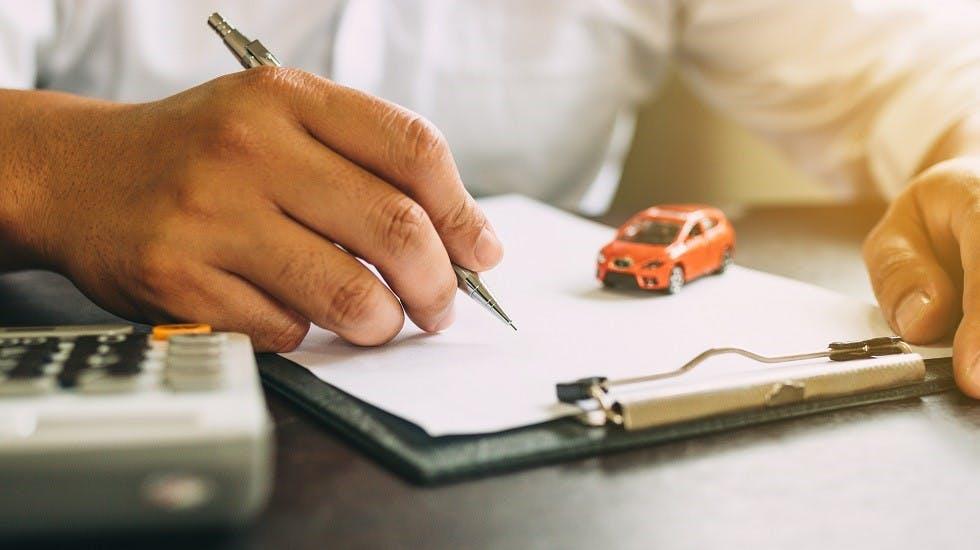 Homme signant un contrat d'assurance auto
