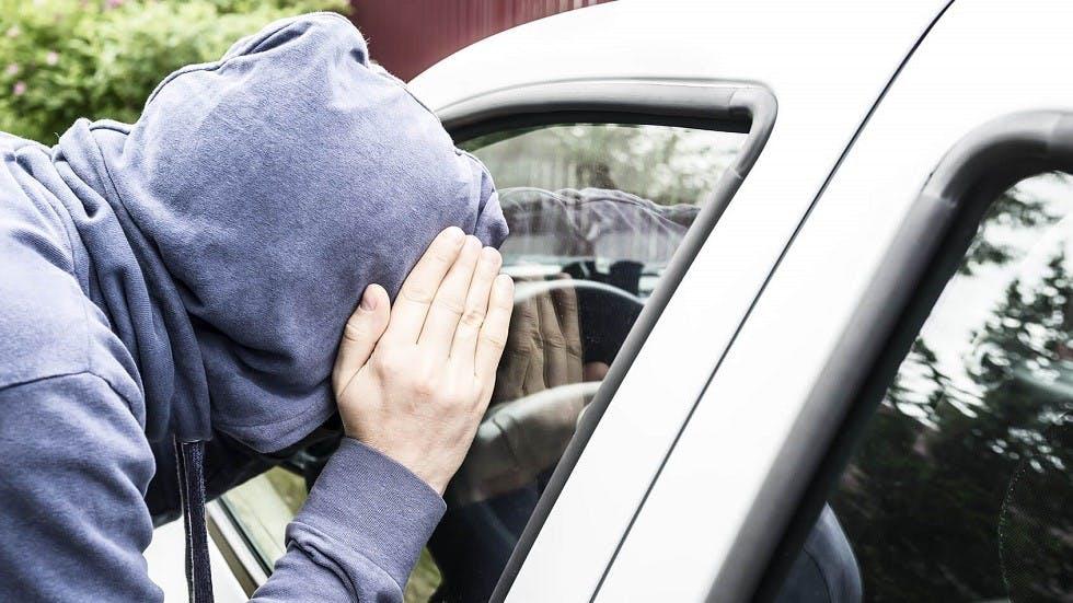 Voleur jetant un regard au travers d'une vitre de voiture