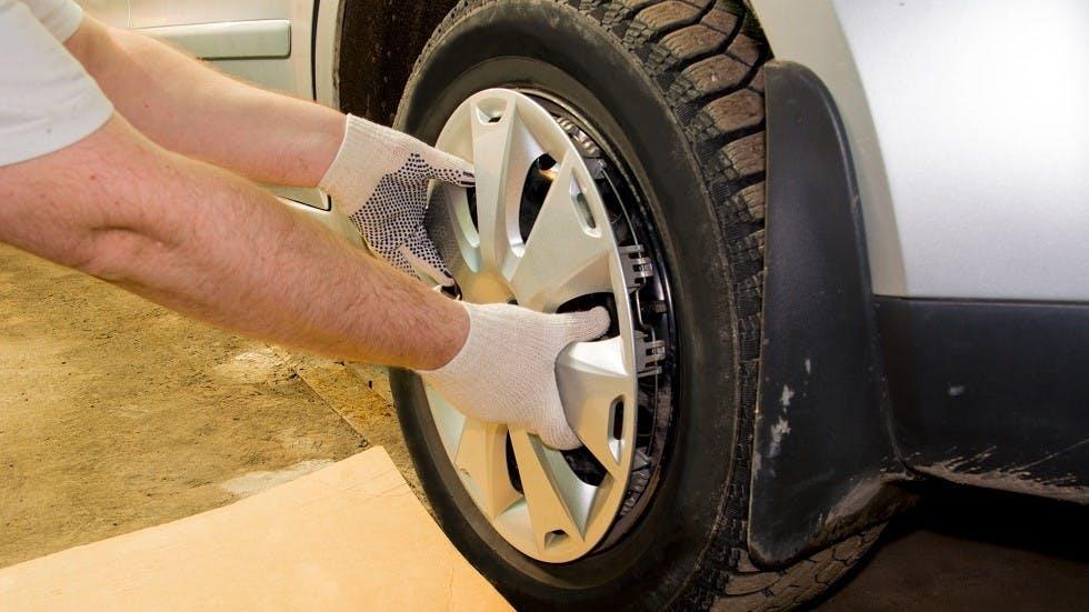Mecanicien retirant l'enjoliveur d'une automobile