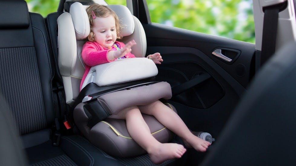 Petite fille jouant dans un siege auto a bouclier d'impact