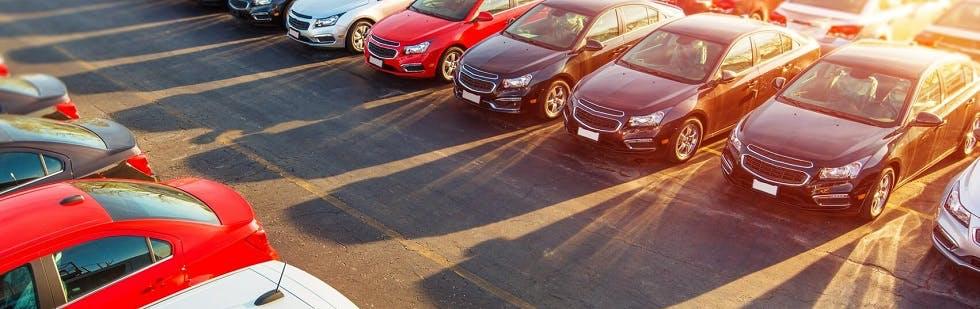 Photographie montrant des rangées de voitures stationnées en plein soleil