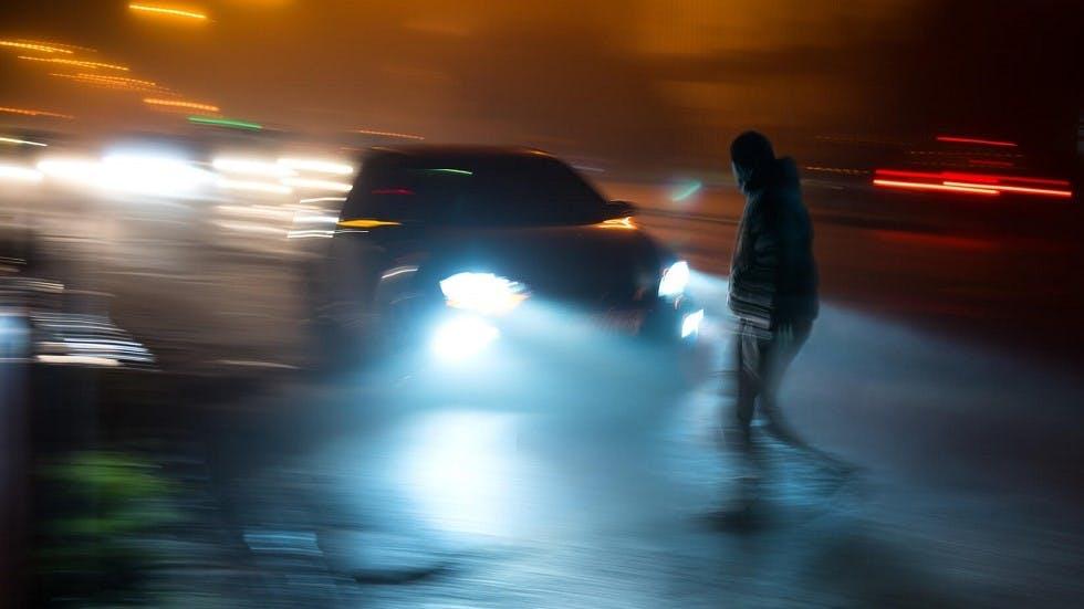 Pieton risquant sa vie en traversant une route de nuit