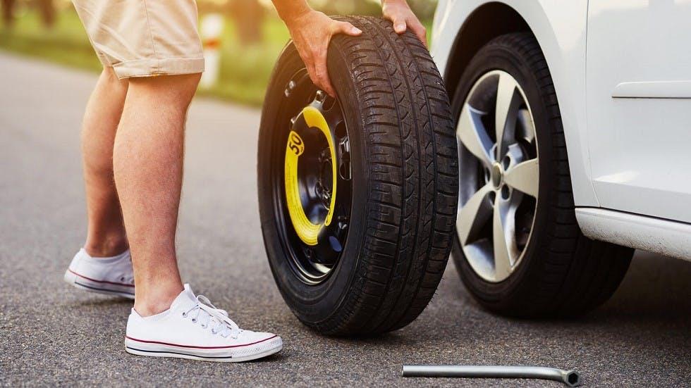 Usager remplacant une roue usagee par sa roue de secours