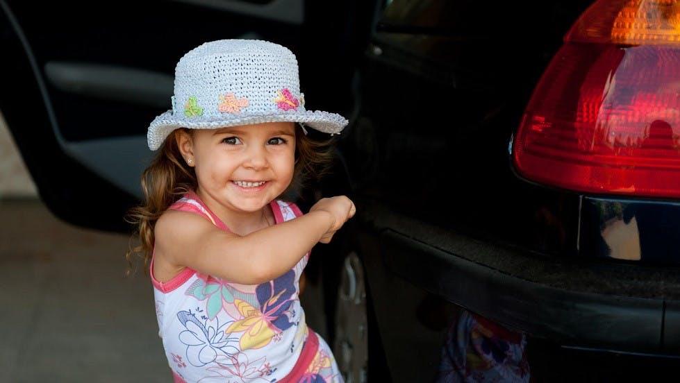Petite fille marchant devant une automobile