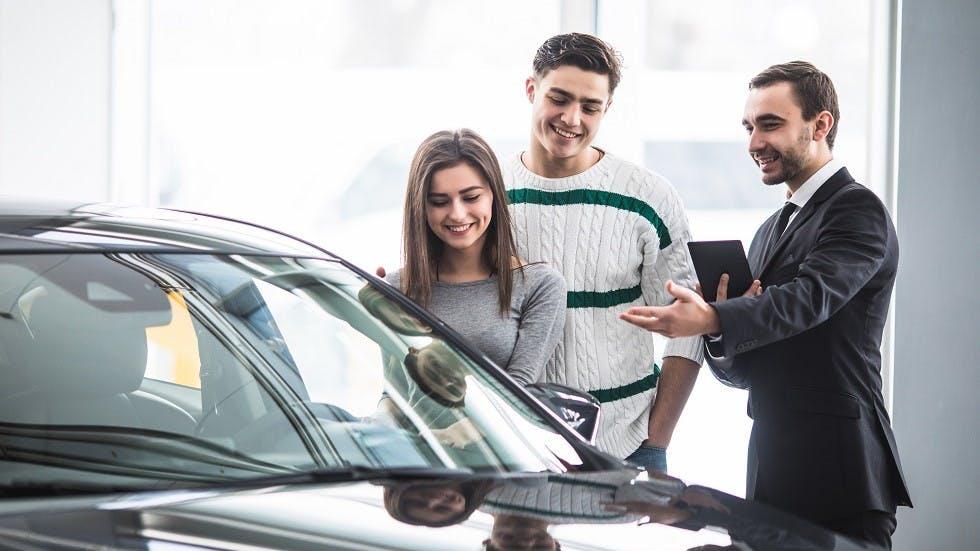 Jeune couple choisissant une auto en loa