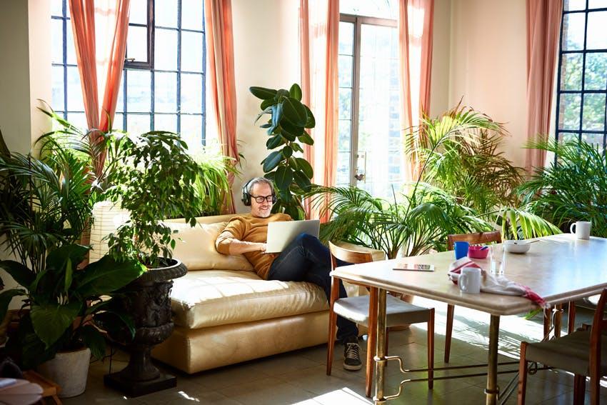 Mężczyzna siedzący w pokoju pełnym roślin