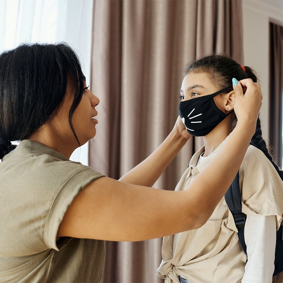 Parent putting mask on daughter