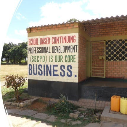 Words painted on wall stating that 'School Based Continuing Professional Development is core for our business'.