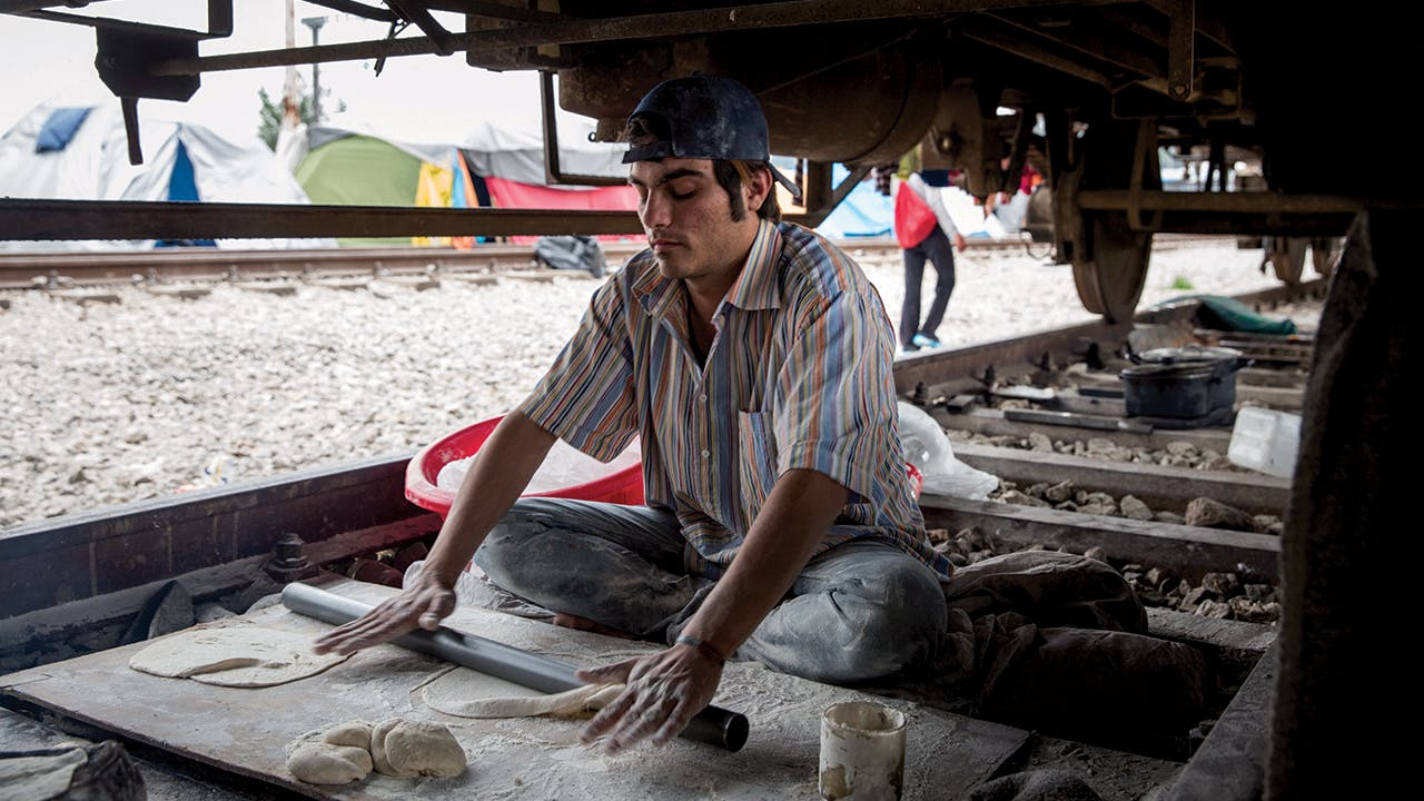 Makmoud Nakarch rolls out dough to make Syrian flatbread in his bakery under a cargo train parked at the Idomeni Camp in Greece. In 2016, after European borders were closed, more than 14,000 asylum-seekers were stranded, living in the area for months.