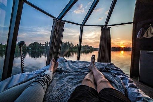 Par ligger i seng i en glassdome med utsikt over innsjø