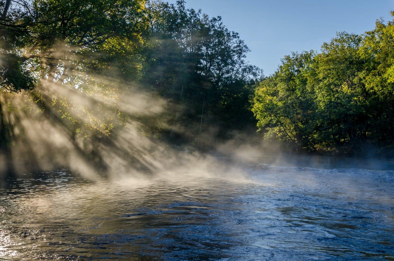 Vackert landskap med sol som lyser över vatten och gröna trädtoppar