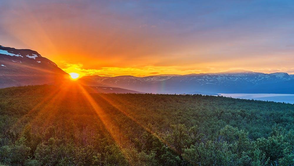 Vacker solnedgång över grönska och berg