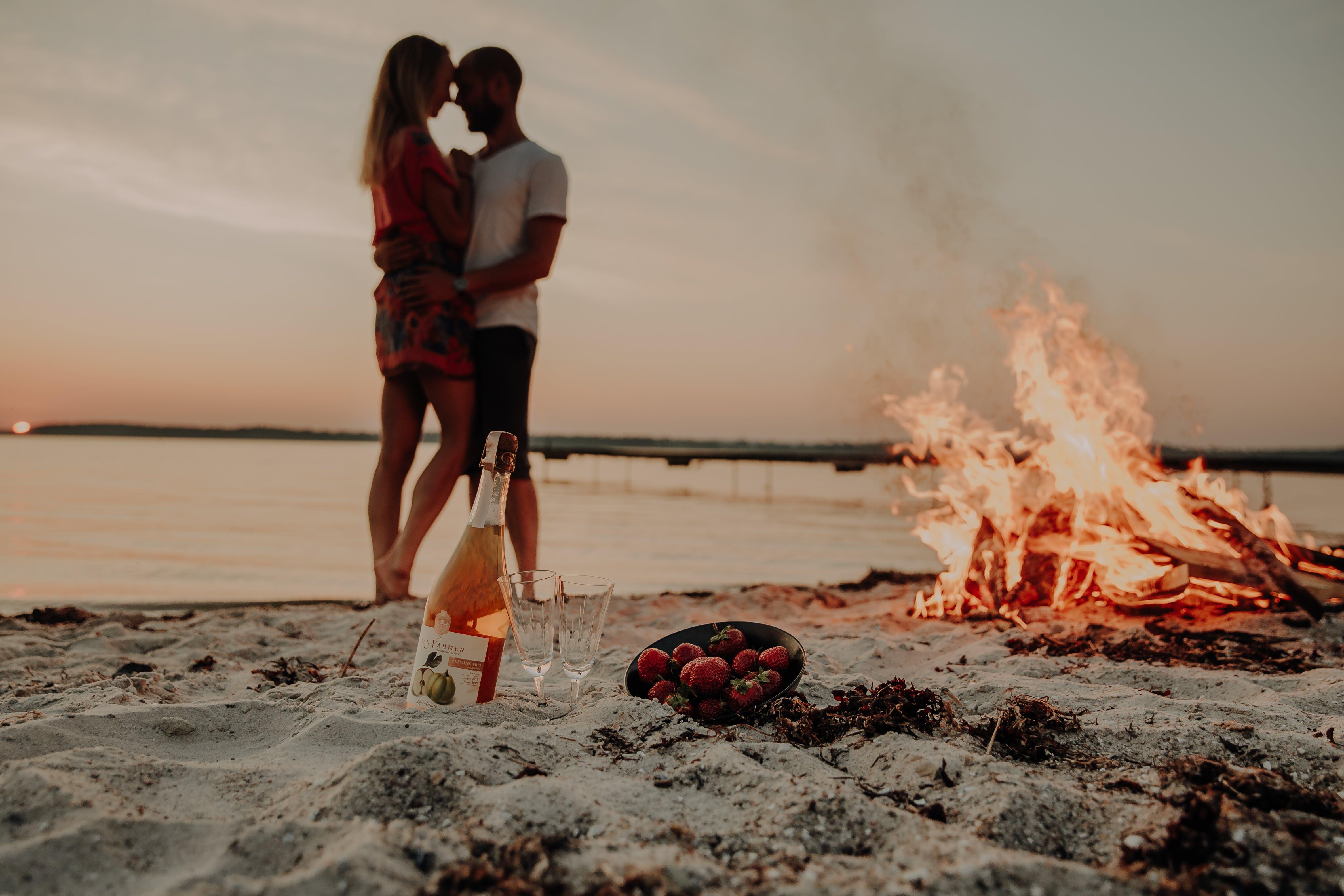 romantic couple on beach with bonfire