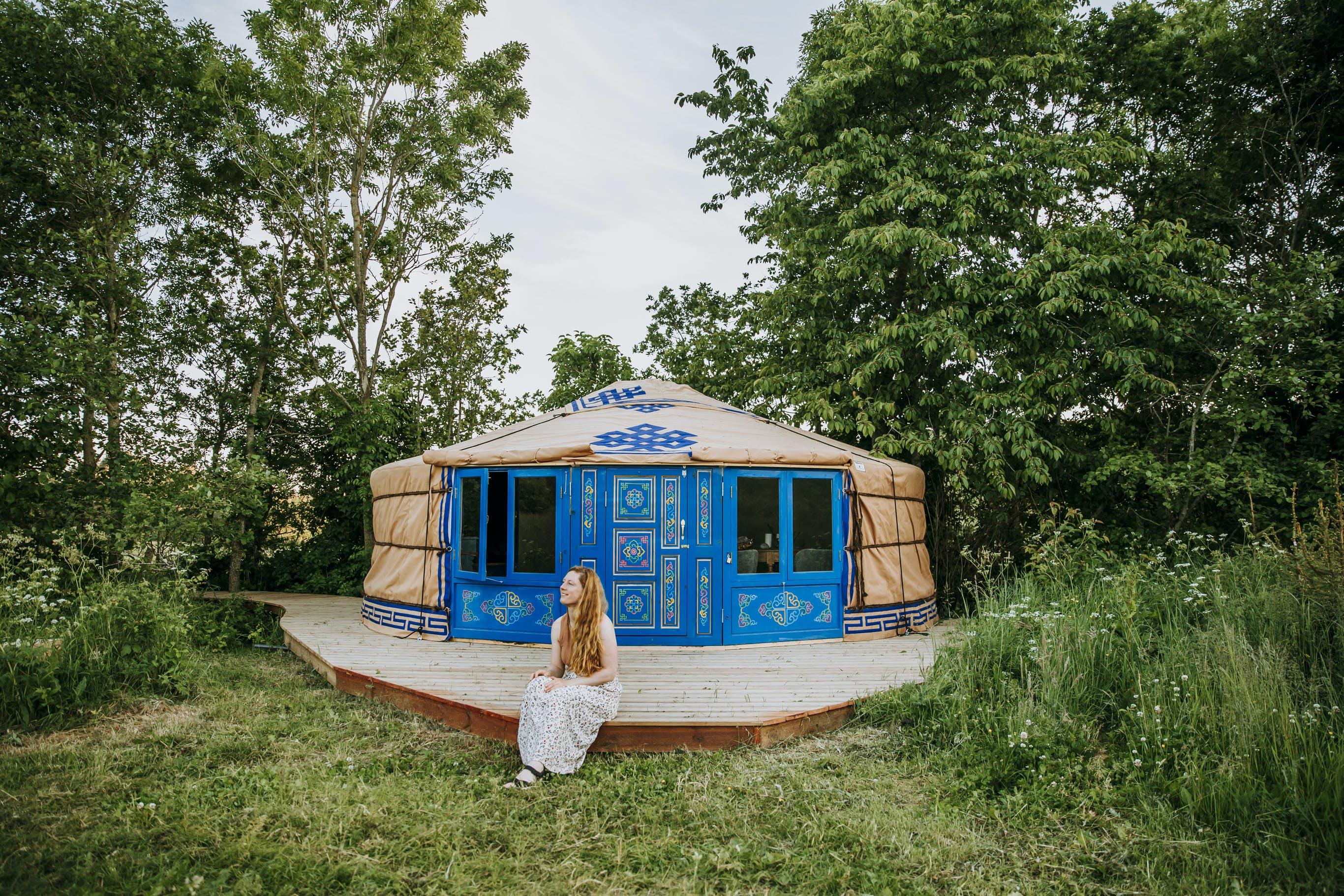 dame sitter utenfor blå mongolsk yurt