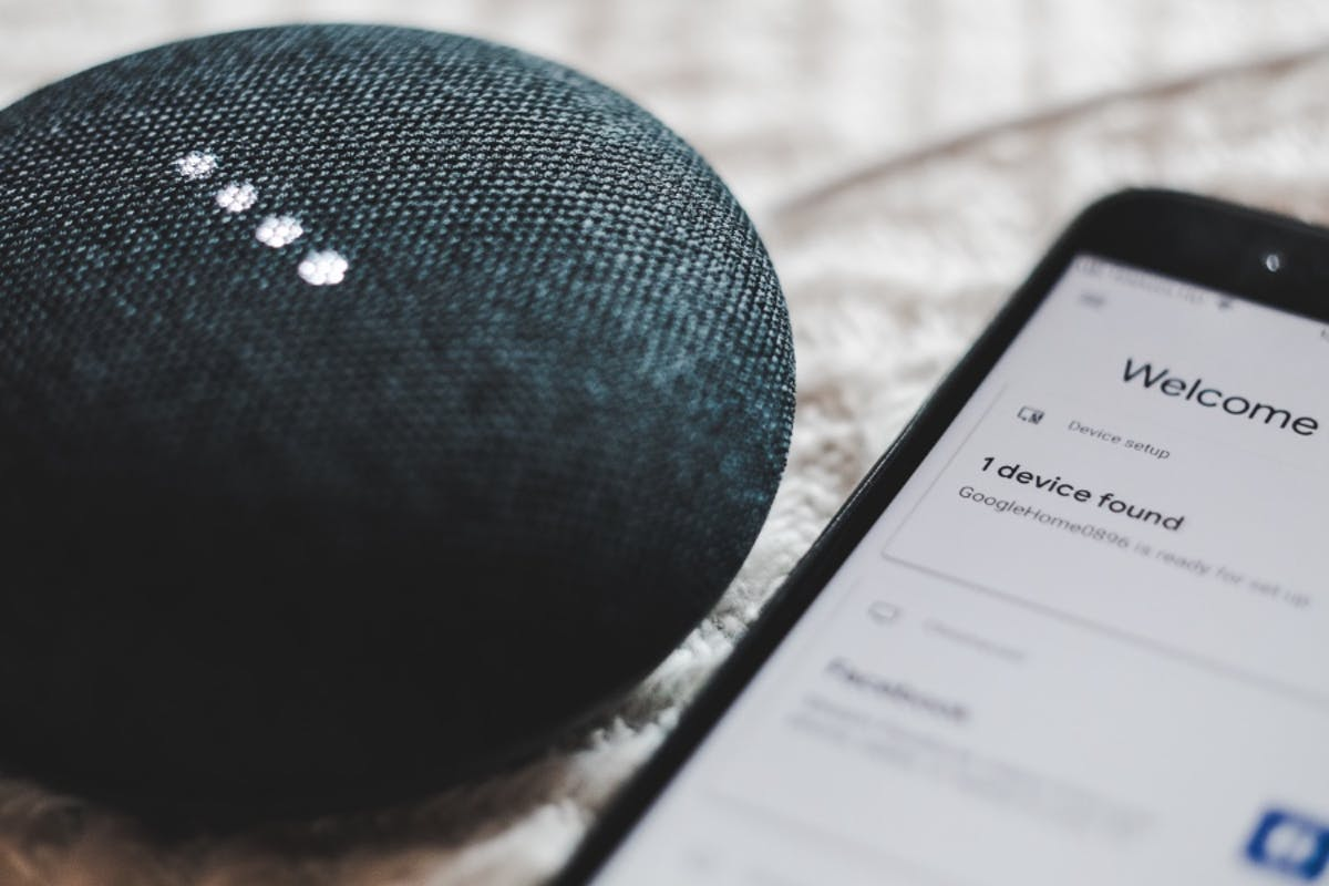 A smartphone connects to a smart home hub to control smart home devices that will save money and save energy.