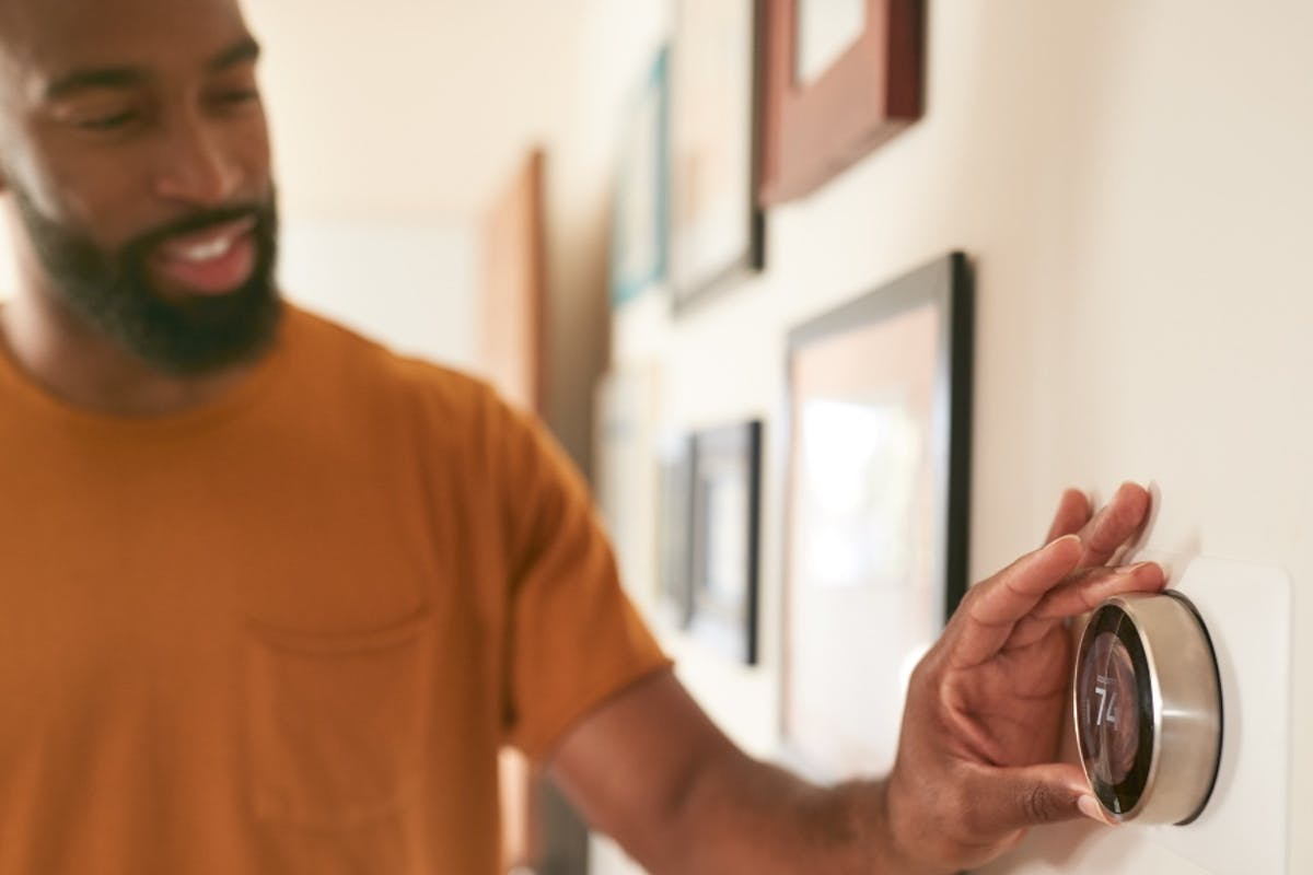 A solar homeowner adjusts their smart thermostat with the recommended thermostat settings for each season.