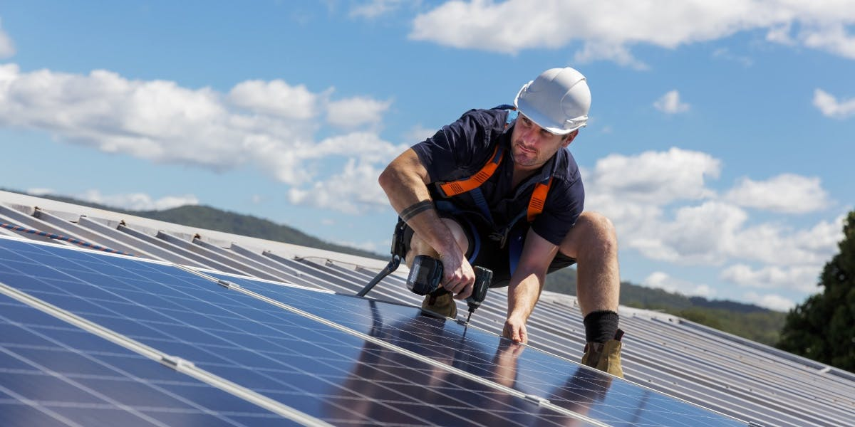Solar Installer Connecting Solar Panels To A Home's Roof