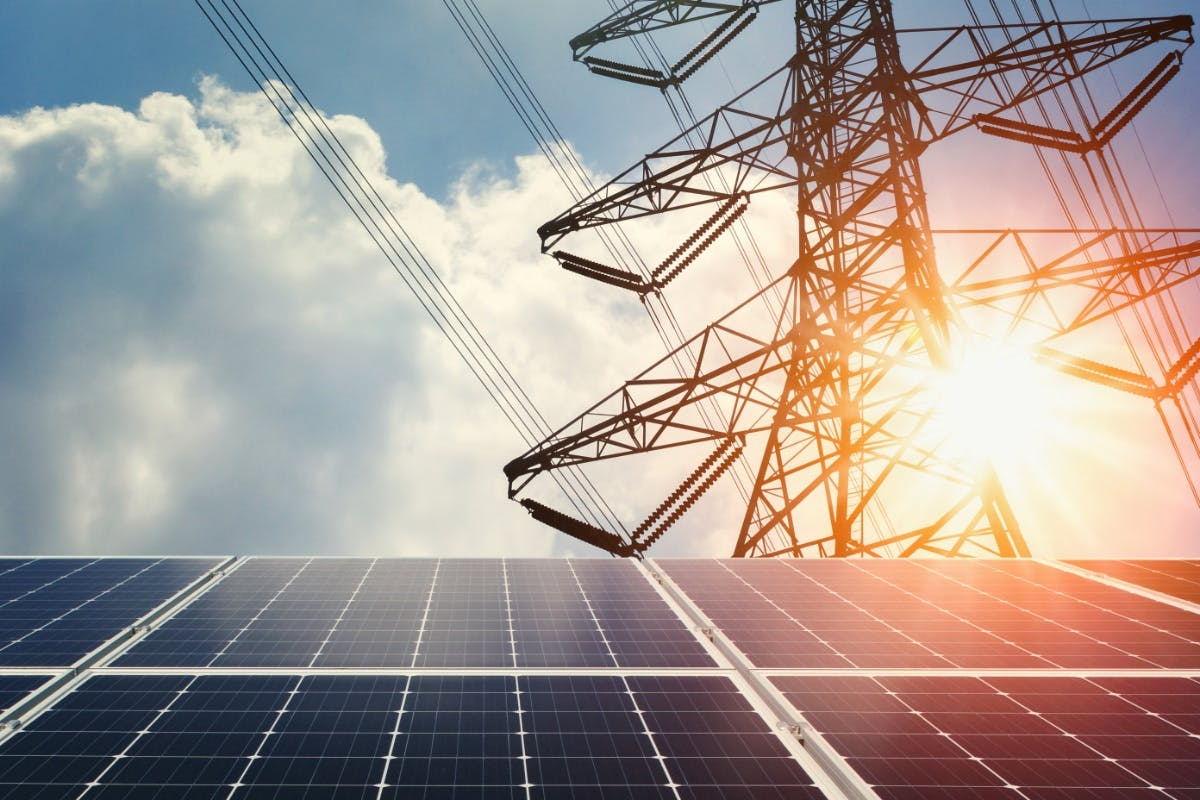 Solar panels below power lines, showing solar power and the grid working together to become a smart grid.