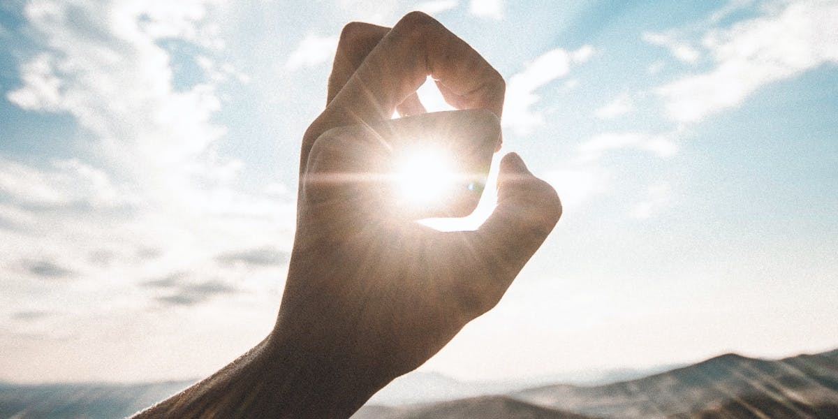 A hand in front of the sun, showing the power of solar energy.