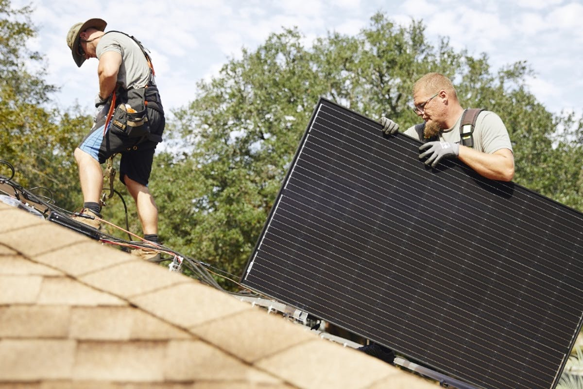 Two Palmetto solar installers adding solar panels to a home's roof.