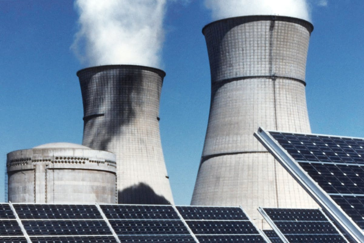 Solar panels in front of a fossil fuel power plant, highlighting the benefits of clean energy.