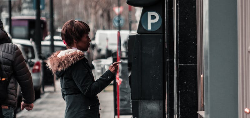 Motorist paying for parking at a meter