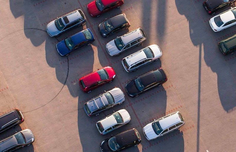 A birds-eye view of a car park full of parked cars