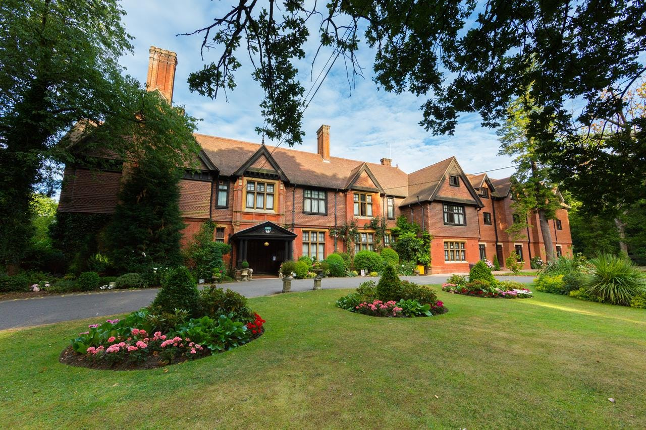 Red brick front and gardens or Stanhill Court Gatwick