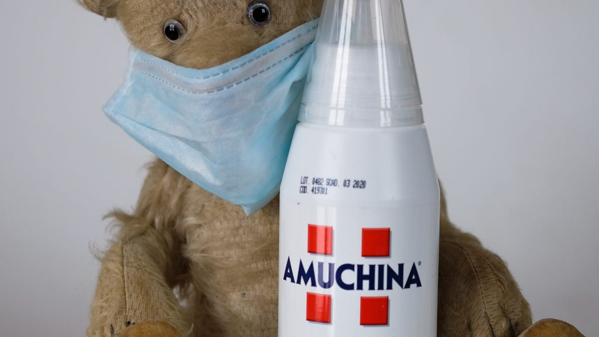 Teddy bear holding a bottle of disinfectant