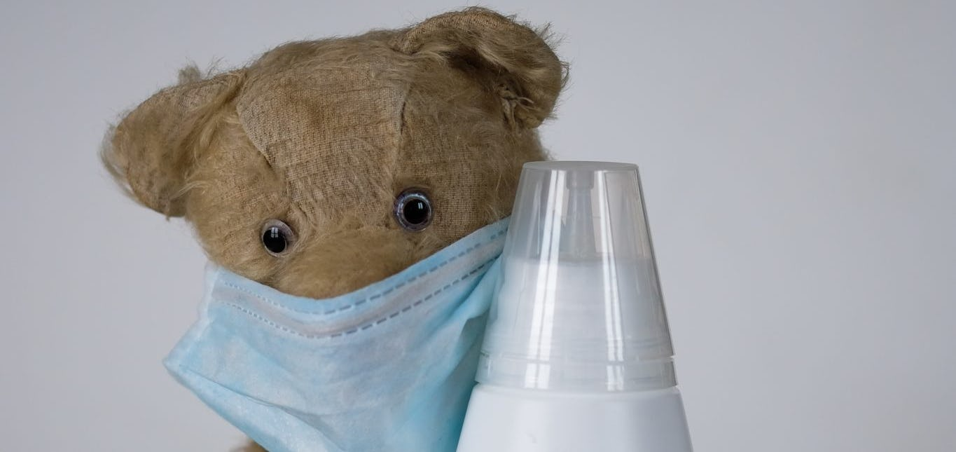 Teddy bear with mask cuddling disinfectant bottle