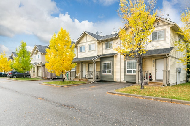 Autumn trees outside a cream-coloured townhome complex