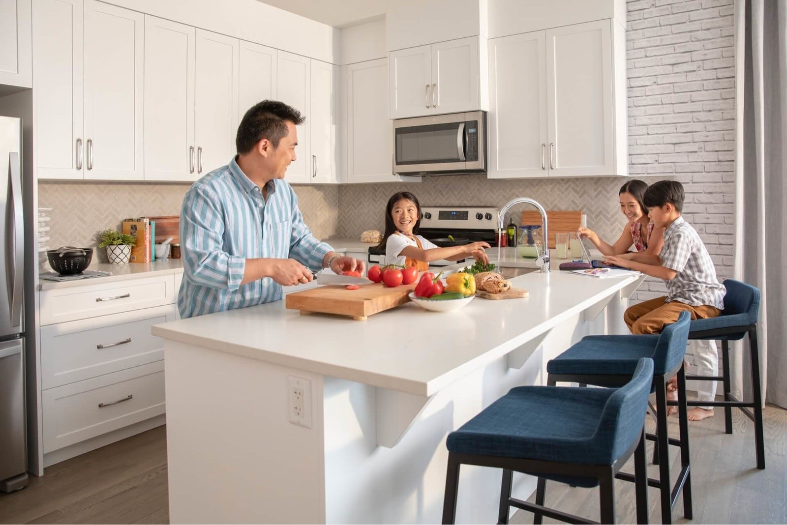 Family preparing food and laughing in kitchen
