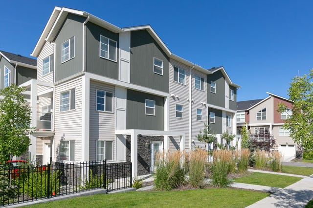 White and grey townhome building with garden out front