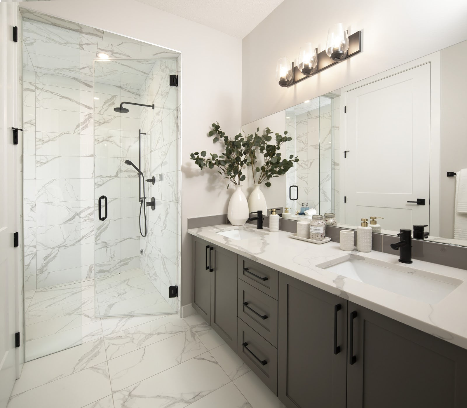 White ensuite bathroom with brown cabinets and curbless shower
