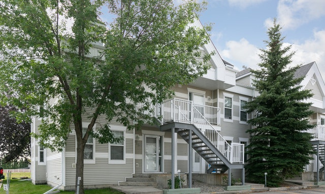 Two-storey grey-coloured townhome complex with trees outside