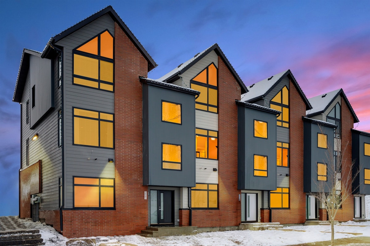 Exterior of a townhome building with brick accents at dusk