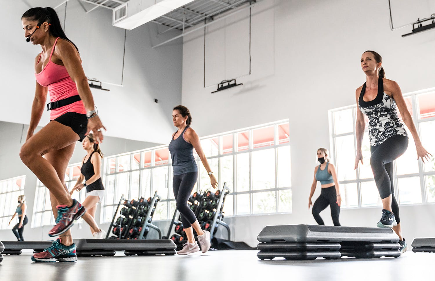 Instructor leading step and sculpt class at the gym