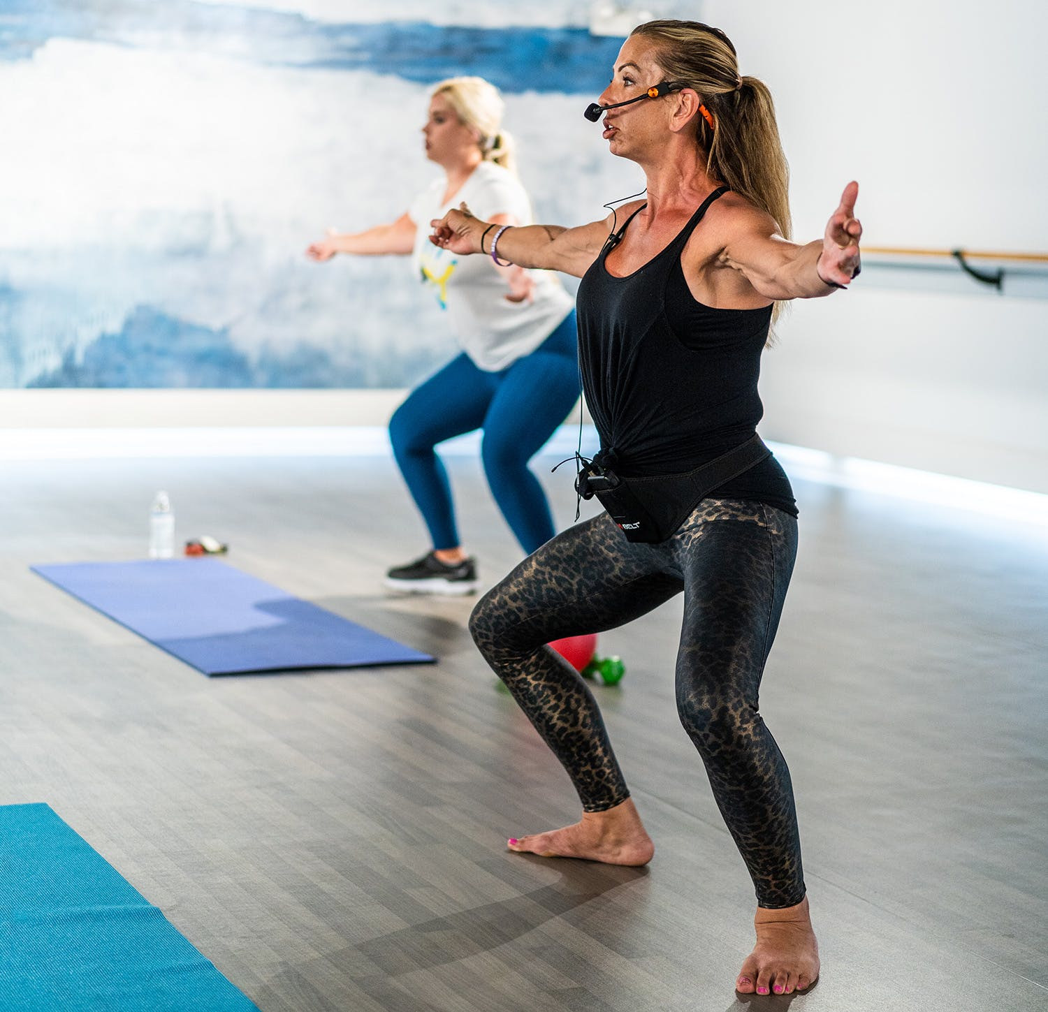 Instructor mid pose leading barre class at gym studio