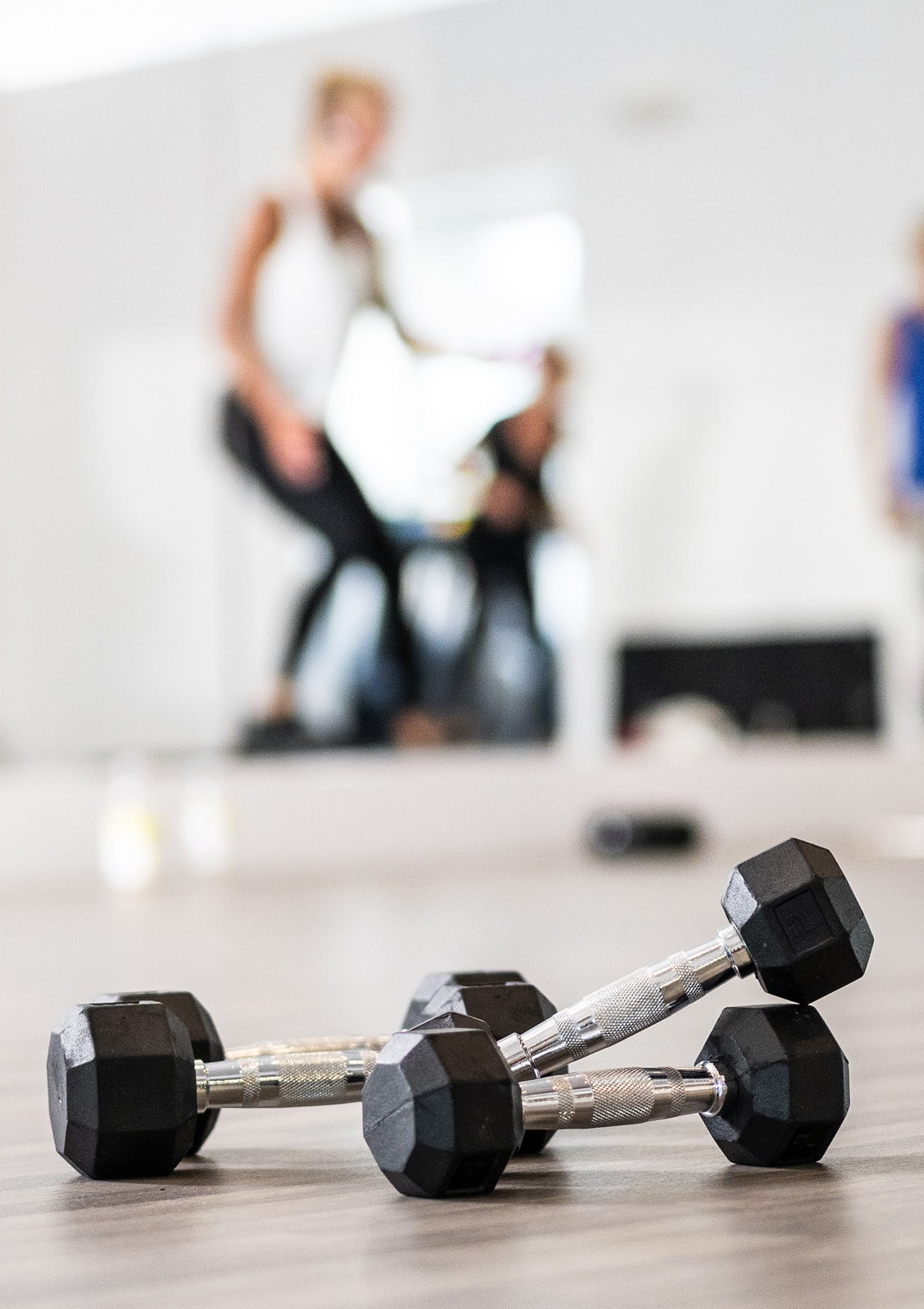 Close-up of weights on floor during interval circuit class