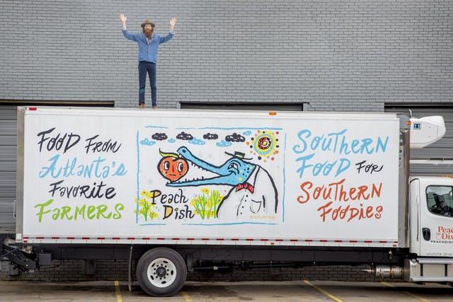 atlanta street artist kyle brooks standing on top of peachdish delivery truck