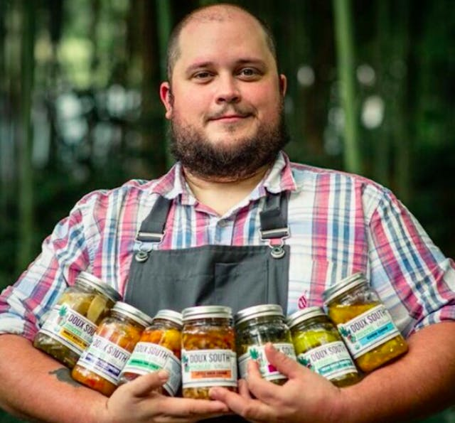 doux south man holding 7 jars of doux south pickles in his arms