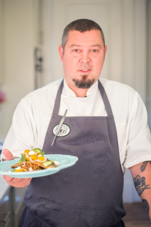 chef terry koval holding his plate of trout with sun gold tomatoes
