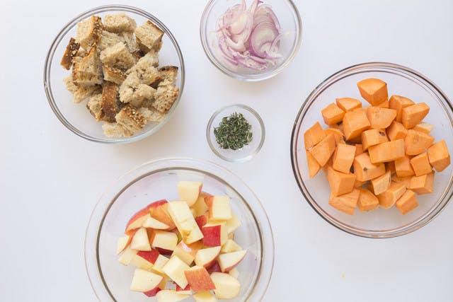 Cubed bread cut sweet potato cut apple sliced shallot thyme leaves