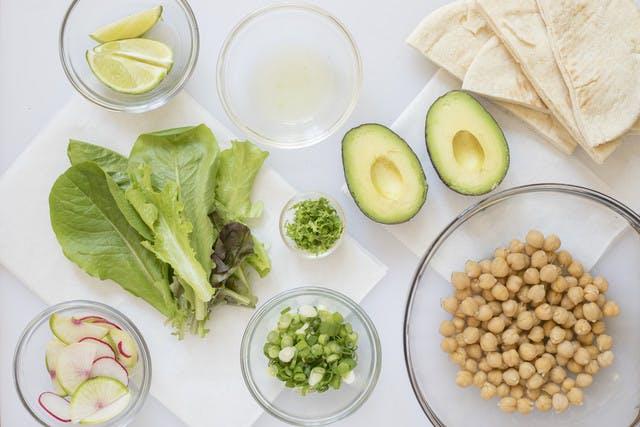Drained chickpeas; halved avocado; lime juice; lime zest; lime wedges; sliced onion; sliced radish; halved pita