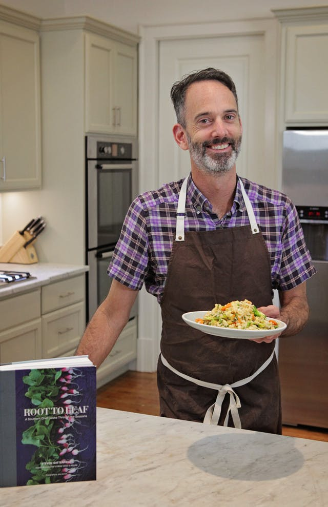 Steven satterfield standing the test kitchen with a plate of broccoli fried rice and his book root to leaf