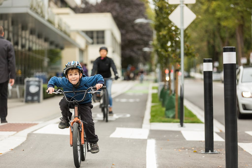A young, elementary school aged child rides an orange bike in a protected bike lane. Their parent rides behind them.