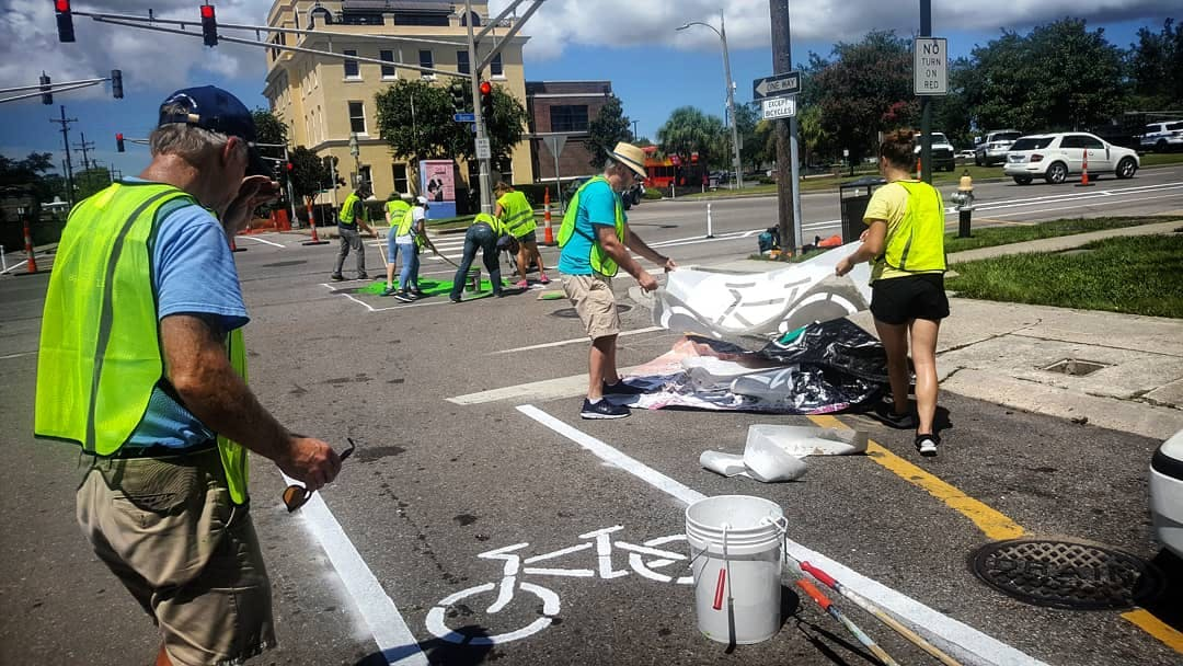 "Volunteers paint ""sharrows"" onto a street in New Orleans to help mark bike routes. (Source: Bike Easy.)"